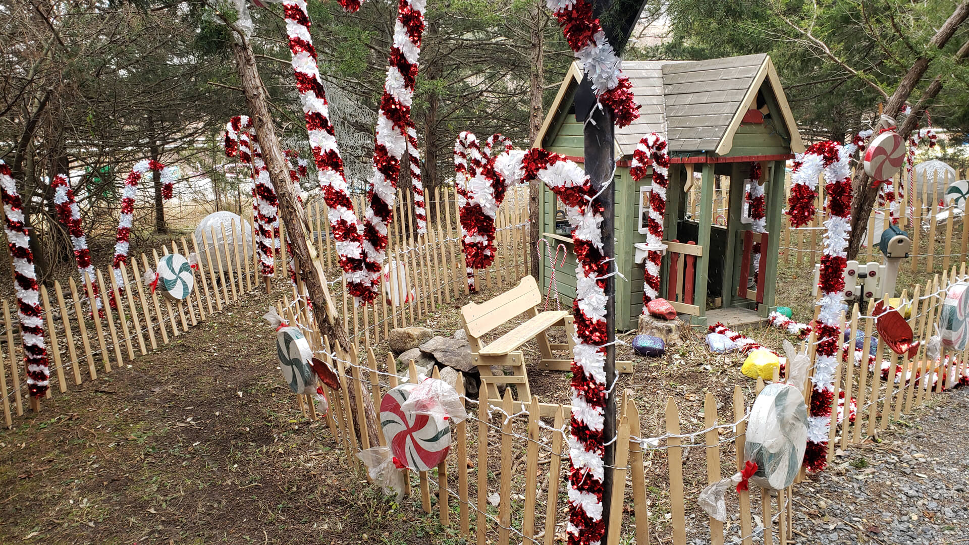 A section of the path through the forest decorated with candy canes and peppermint candies, along with a tiny cottage and bench