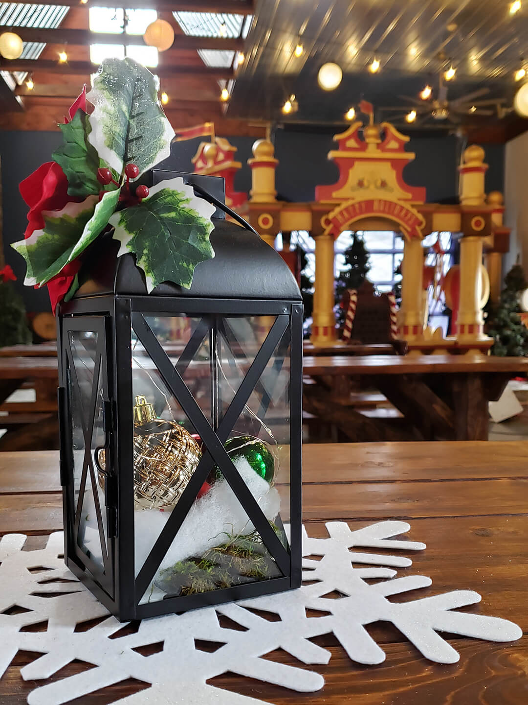 A table centerpiece featuring a lantern, holly, and ornaments, with Christmas decorations in the background