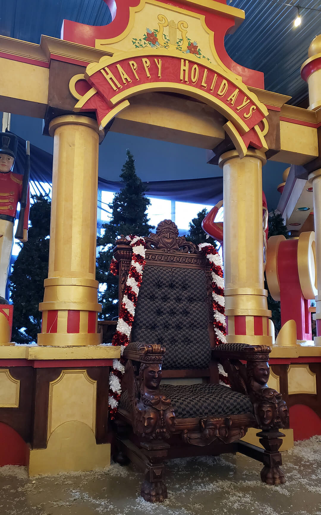 "A large, regal chair for Santa centered under an archway reading ""Happy Holidays"""