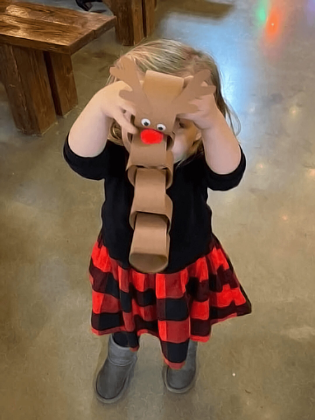 A toddler proudly holding up a simple reindeer arts and crafts project made from construction paper