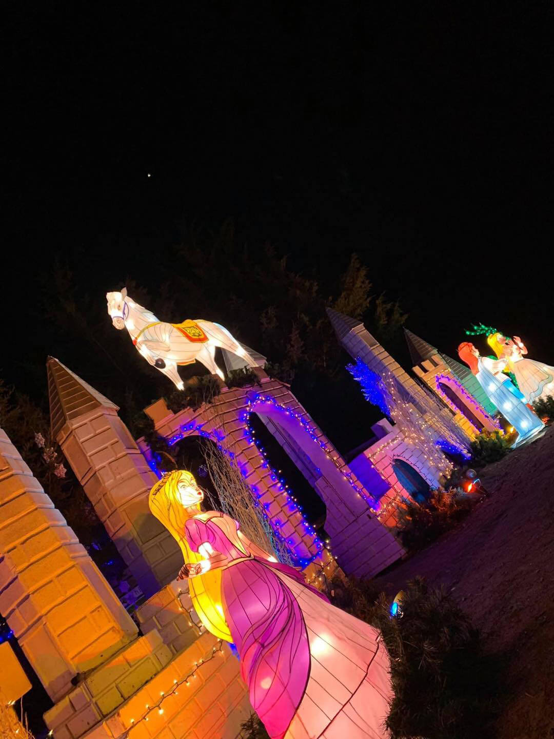 A towering castle facade with fairy tale characters, lit up colorfully at night