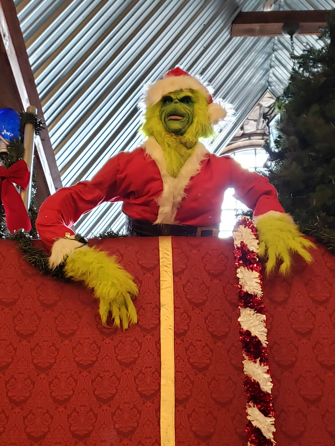 A life-sized figure of the Grinch, dressed as Santa, scowling and leaning over a balcony