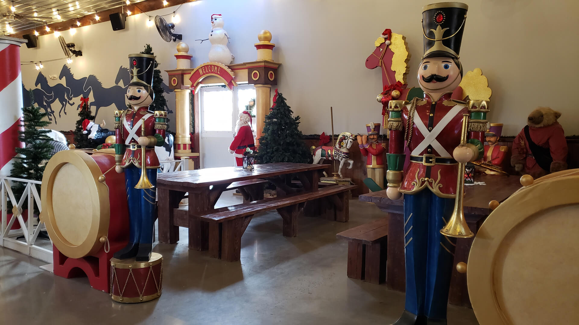 Indoor seating surrounded by large-scale Christmas decorations including life-size toy soldiers, Santa, and candy cane pillars